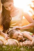 stock photo of caress  - Mother is caressing her child resting on knees outdoor in nature - JPG