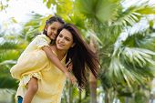 picture of piggyback ride  - Young Indian woman giving piggyback ride to her daughter - JPG