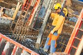 stock photo of concrete pouring  - builder worker with boom pump pouring concrete on metal rods reinforcement of formwork - JPG
