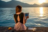 pic of sea-scape  - Young woman reading book and looking at beautiful sunrise on the pier with sea and mountains on background - JPG
