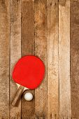 foto of ping pong  - Red ping pong paddle and ball on vintage wooden background - JPG
