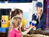 stock photo of sisters  - Sisters buying snacks from female concession worker at cinema counter - JPG