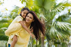 picture of indian  - Young Indian woman giving piggyback ride to her daughter - JPG