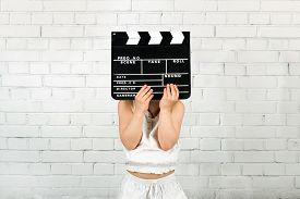 stock photo of clapper board  - Kid cover face with clapper board against brick wall - JPG