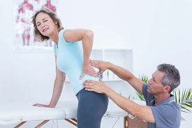 image of physiotherapist  - Physiotherapist examining his patient back in medical office - JPG