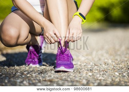 young woman in fitness wear tying shoelaces outdoors