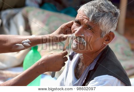 An Unidentified Man Shaves From A Street Barber At The Pushkar Fair