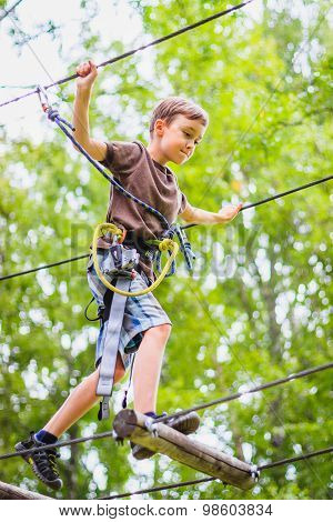 Young boy climbing in adventure park