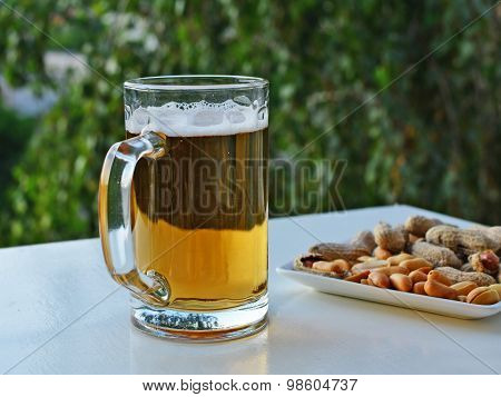Mug Of Light Beer And Peanuts On The Table