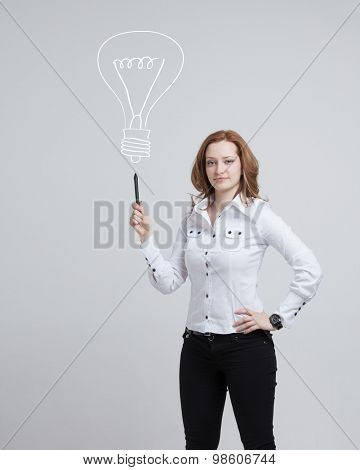 Young businesswoman drawing and idea lamp on the whiteboard