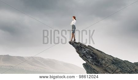 Businesswoman with arms crossed on chest standing on edge of rock