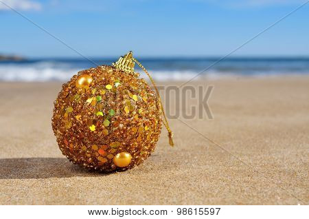 an ornamented golden christmas ball on the sand of a beach