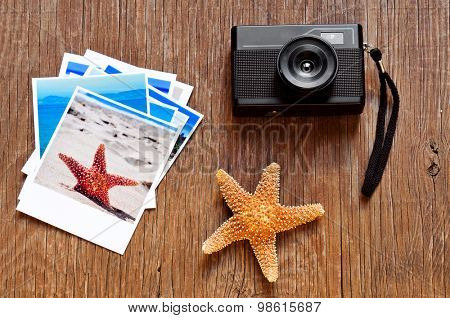 high-angle shot of a retro camera, a starfish and some photos, shot by myself, of beach scenes, placed on a rustic wooden table