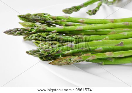 closeup of some raw asparagus in a white plate on a white surface
