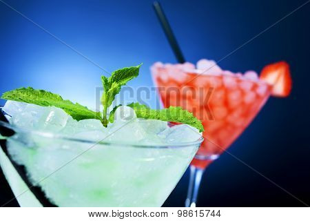 closeup of some cocktail glasses with beverages of different colors garnished with mint leaves and a strawberry over a blue lighted background