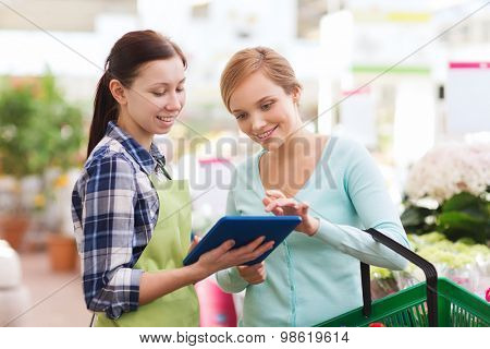 people, gardening, shopping, sale and consumerism concept - happy gardener with tablet pc helping woman with choosing flowers in greenhouse