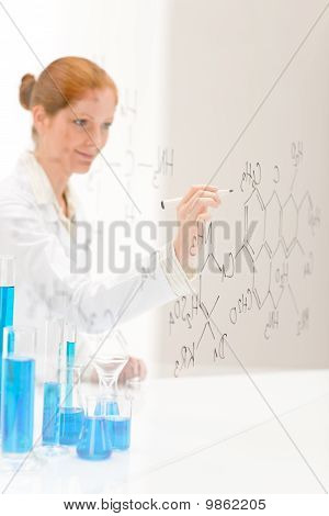 Woman Scientist In Laboratory Write Chemical Formula