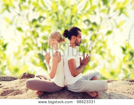 fitness, sport, meditation and lifestyle concept - smiling couple making yoga exercises sitting outdoors
