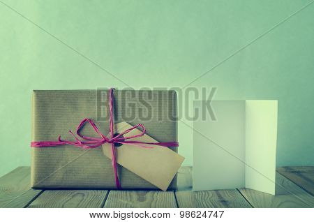 Wrapped And Labeled  Brown Paper Gift With Raffia Bow And Blank Card