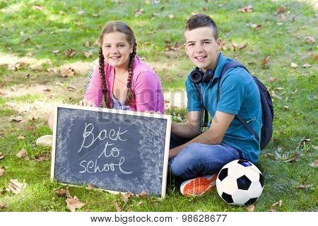 School kids sitting on the grass holding a blackboard