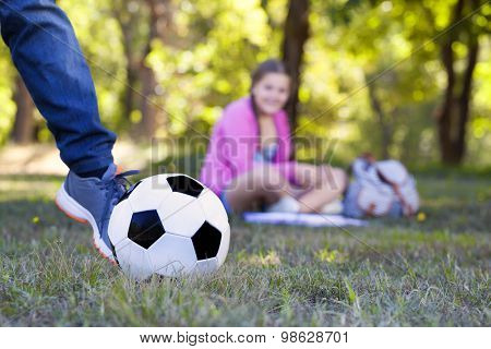 Image of a boy kicking a ball at the park