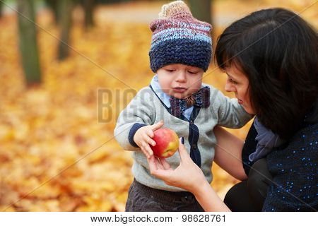 mom gives son red apple