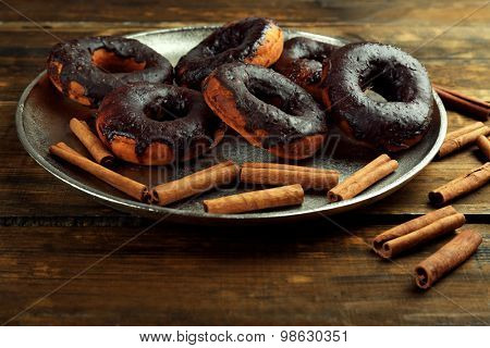 Delicious doughnuts with chocolate icing and cinnamon on table close up