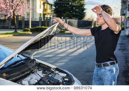 Handsome young man trying to repair a car engine
