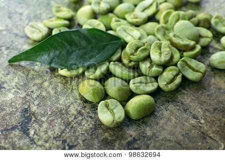 Heap of green coffee beans with leaf on table close up