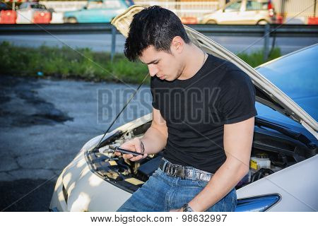 Man trying to repair car and seeking help on phone