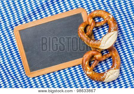 Empty Blackboard With Pretzels On A Bavarian Diamond Pattern