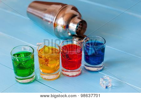 Blue, yellow, green, red alcohol or alcohol-free cocktail with ice cubes and shaker on a bar counter