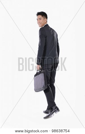Full body Portrait of a successful back young business man carrying a suitcase walking on white background