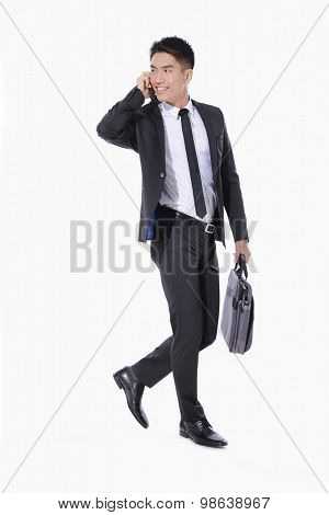 successful young business man walking carrying a suitcase , speaking on cellphone