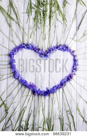 Beautiful cornflowers in shape of heart on wooden background