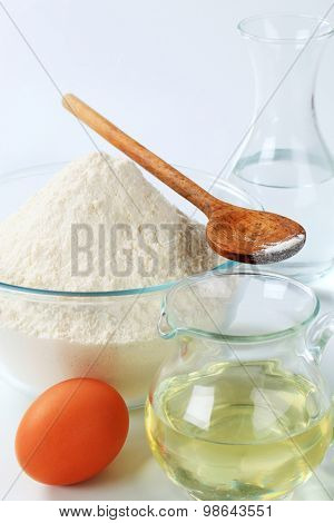 wheat flour,  carafe of cold water, jug of sunflower oil and an egg