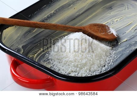 heap of desiccated coconut in greased baking pan