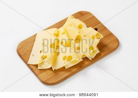 thin slices of emmental cheese on wooden cutting board