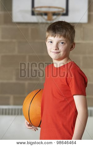 Portrait Of Boy Holding Basketball In School Gym