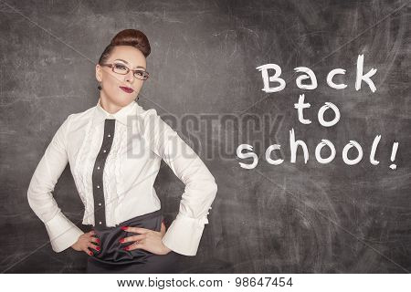 Happy Teacher On The Blackboard Background