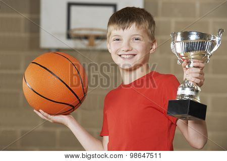 Boy Holding Basketball And Trophy In School Gymnasium