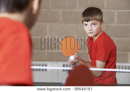 Two Boys Playing Table Tennis Match In School Gym