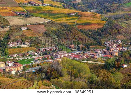 Small town among autumnal hills and vineyards of Piedmont, Northern Italy.