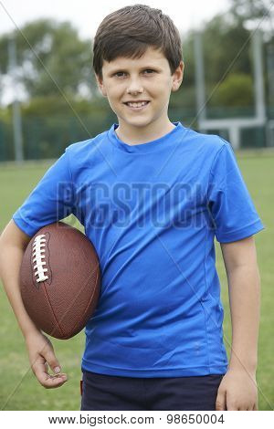 Portrait Of Boy Holding Ball On School Football Pitch