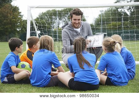 Coach Giving Team Talk To Elementary School Soccer Team