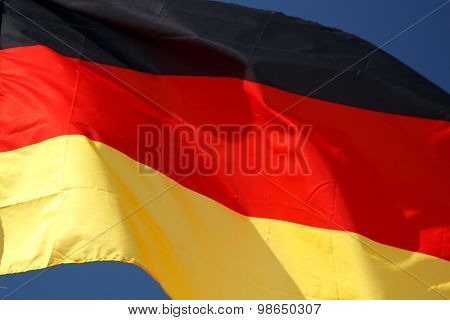 Flag of Germany with wrinkles and seams expanded in the breeze