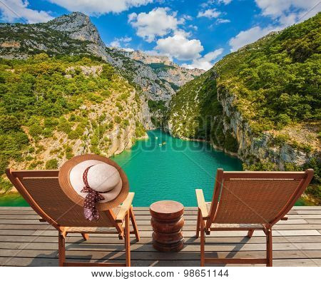 Travel across Provence. Two wooden chaise lounges on platform at the lake Verdon