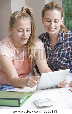 Female Home Tutor Helping Girl With Studies Using Digital Tablet