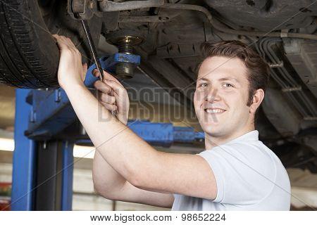 Portrait Of Mechanic Working On Wheel Underneath Car