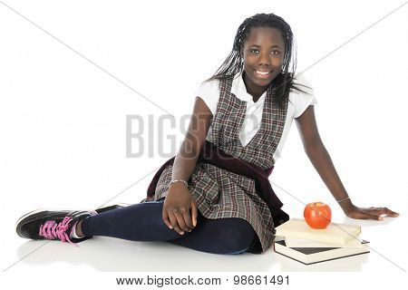 A happy tween schoolgirl relaxed on the floor in her school uniform, a small stack of books by her side.   On a white background.